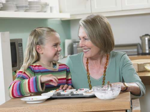 Granddaughter with her Grandmother in a Kitchen, Decorating Cup Cakes with Candy