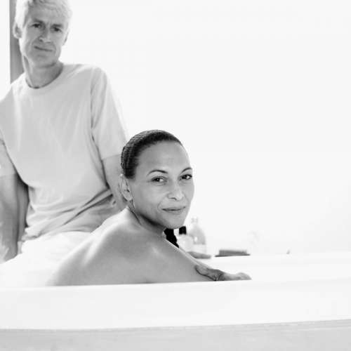 woman relaxing in a bath with her husband sitting on the side