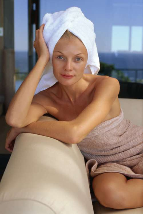 Woman wrapped in towels posing on sofa