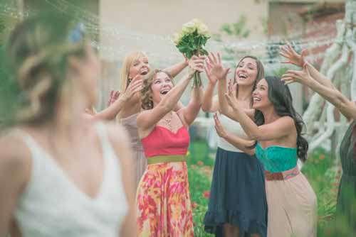 Happy Girls Catching Brides Bouquet At Outdoor Wedding