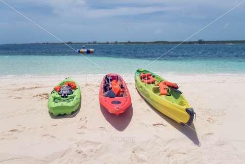 Three Ocean Kayaks On A Summer Beach