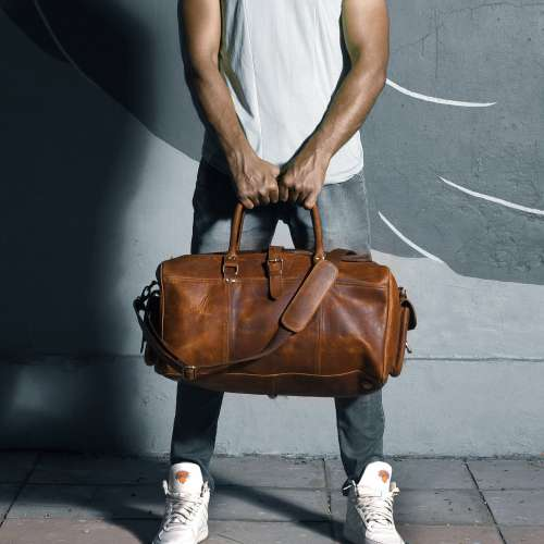 Man Holding His Leather Travel Bag Photo