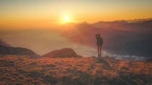 Person Watching Sunset Above The Clouds Photo