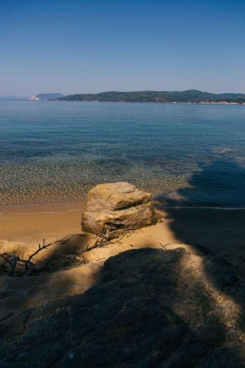 Rock Sits Upon Sandy Sea Shore Photo