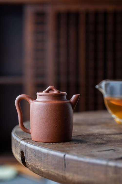 A Dark Ceramic Teapot On A Wooden Table Photo