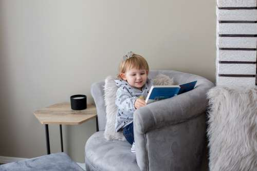 Young Girl Reads In Comfy Chair Photo