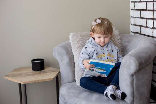 Little Girl In Her Reading Chair Photo