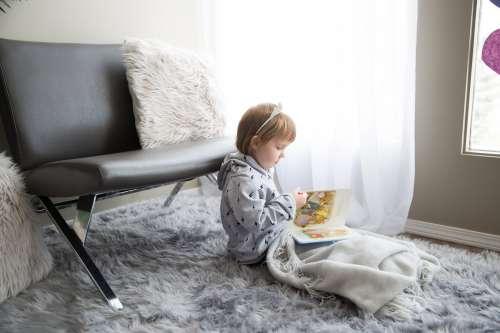 Little Girl Under A Blanket Reading Photo