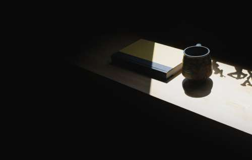Cup And Book On A Shelf In Shadow Photo
