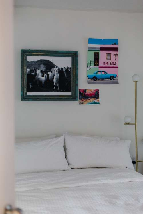 White Bed With Ecclectic Art On The Wall Photo
