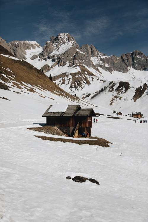 Wooden Cabin Below Snowcapped Mountains Photo