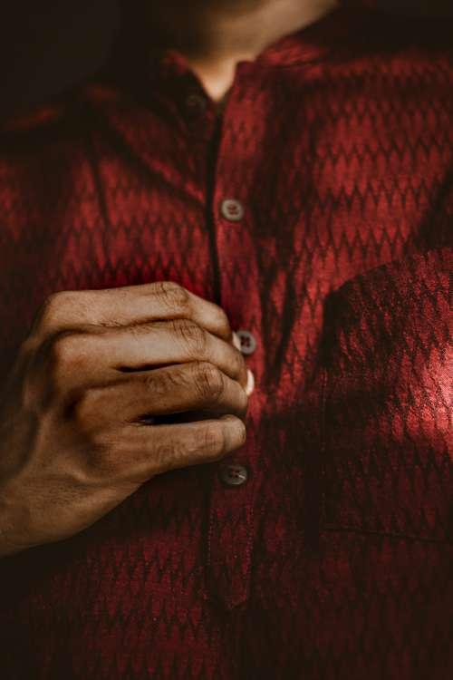 Man Buttoning A Dark Red Shirt Photo