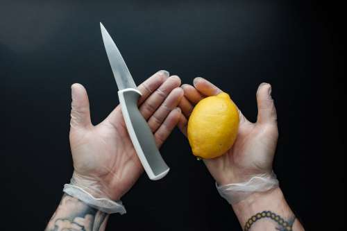 Gloved Hands Holding A Knife And Lemon Photo