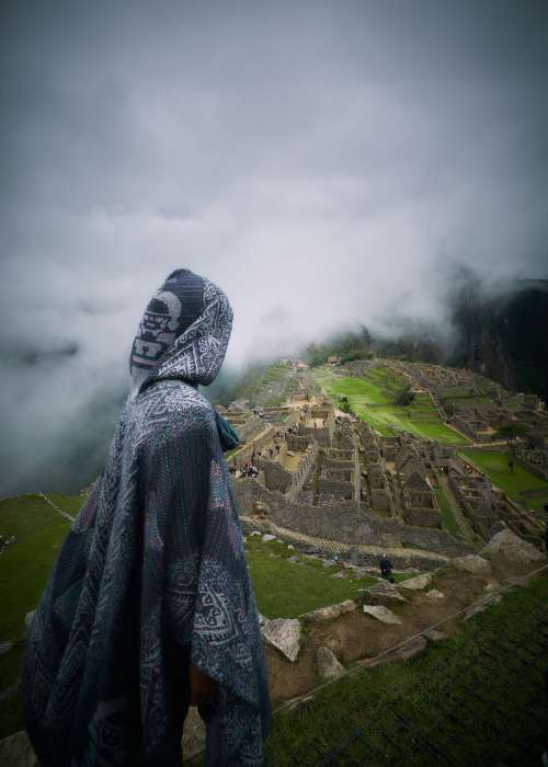 Hooded Person Overlooking Ruins Photo