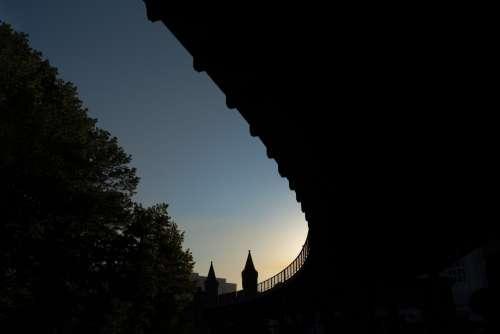 Sun Sets Over The Horizon Above A Bridge Photo