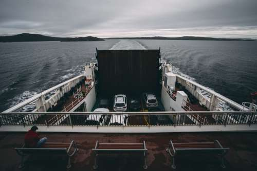 Sitting Atop A Ferry Travelling Across Water Photo