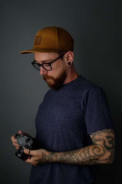 Tattooed Man Holding Film Camera Photo