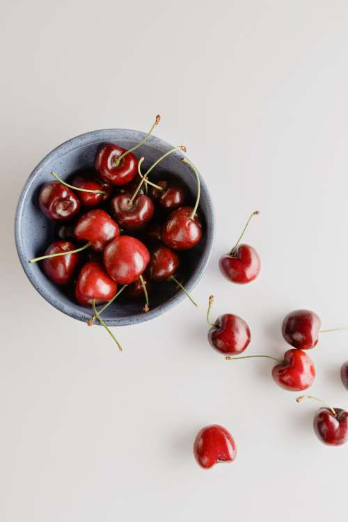 Bowl Of Red Cherries On A White Background Photo