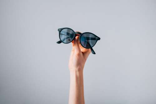 Pair Of Sunglasses Held In Front Of Grey Background Photo