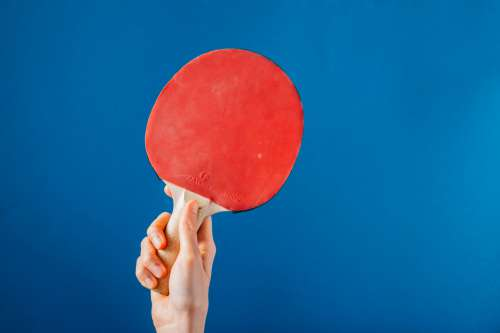 Hand Holding Ping Pong Paddle On Blue Background Photo