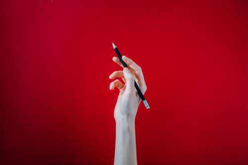 Hand Holding Black Pencil On Red Background Photo