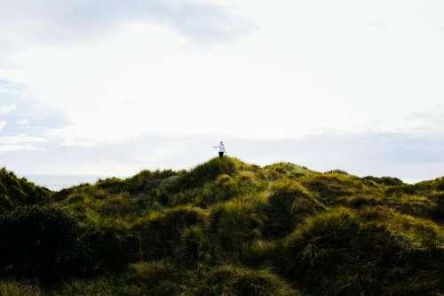 Woman Walks Across Grassy Dunes Photo