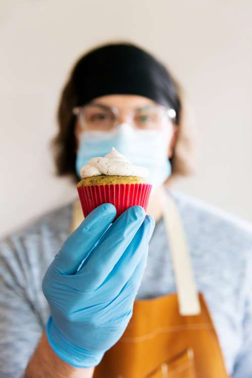 Holding Up A Cupcake In Gloves And Mask Photo