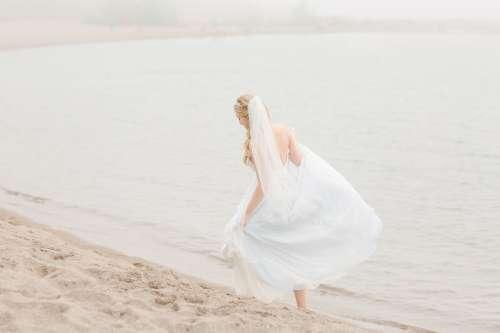 Bride Taking A Walk Along The Beach Photo