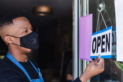 Man Wearing Face Mask Flips Open Sign Photo