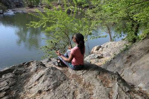 Young Woman sitting in lotus yoga pose near lake