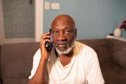 Older Man talking on smartphone at home - looking at camera
