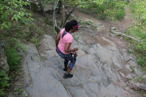 Young Woman in yoga pants using rock stairs with trees in the forest