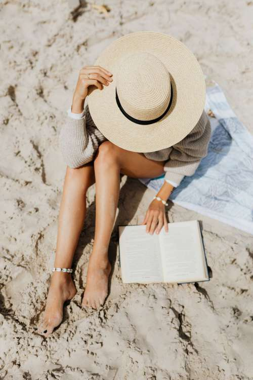 A woman reads on the beach in the summer