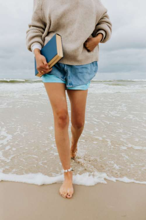 A young woman with a book on the seashore