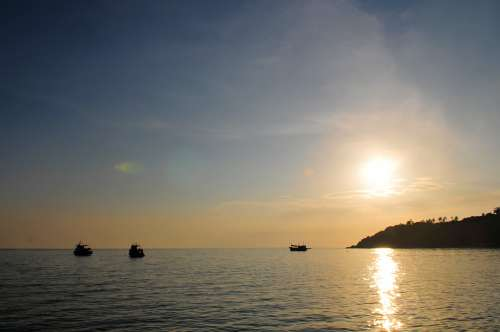 Sunset Over Ocean With Fishing Boats And Island