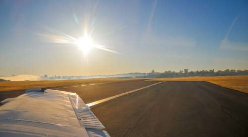 Plane Wing And Runway At Sunrise