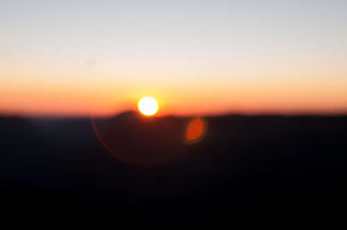 Out Of Focus Blur Of Sunrise Over Mountains