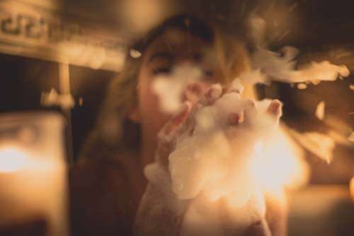 Girl Playfully Blowing Soap Suds With Candles
