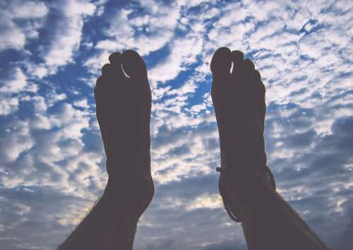Mans Feet In The Air With Blue Cloudy Sky