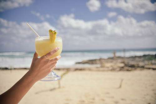Womans Hand Holding Cocktail On Beach