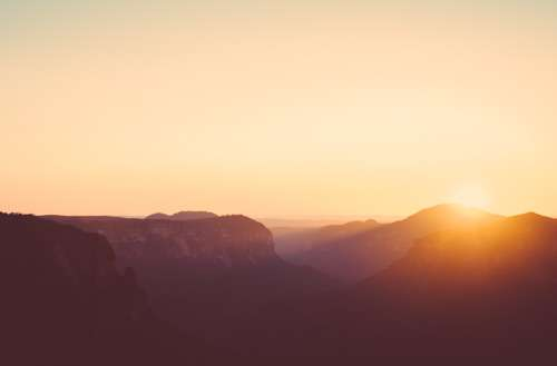 Sun Rising Over Blue Mountains And Canyon