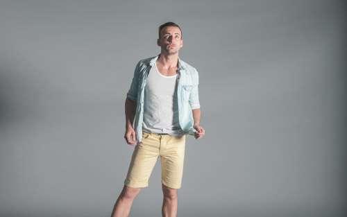 Stylish Man On Grey Background Wearing Summer Yellow Shorts And Shirt