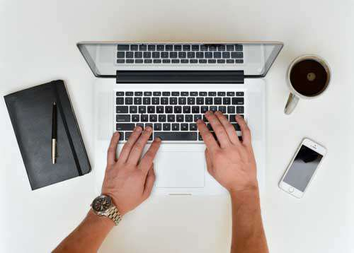 Mans Hands Typing On Laptop With Smartphone, Book And Coffee