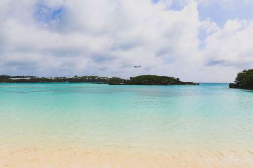 Plane Glides Above Tropical Beach Photo