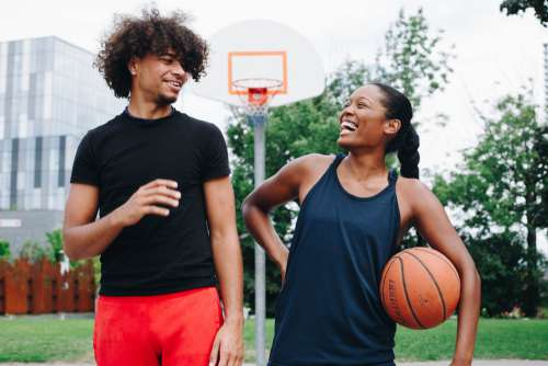 Young Man And Woman Share Laugh On The Court Photo