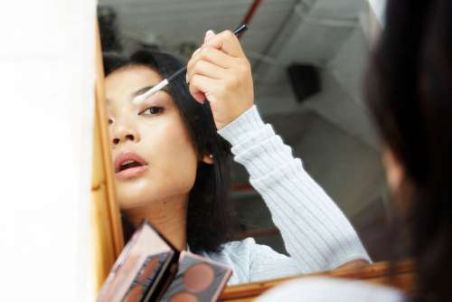Mirror View Of Putting On Makeup Photo