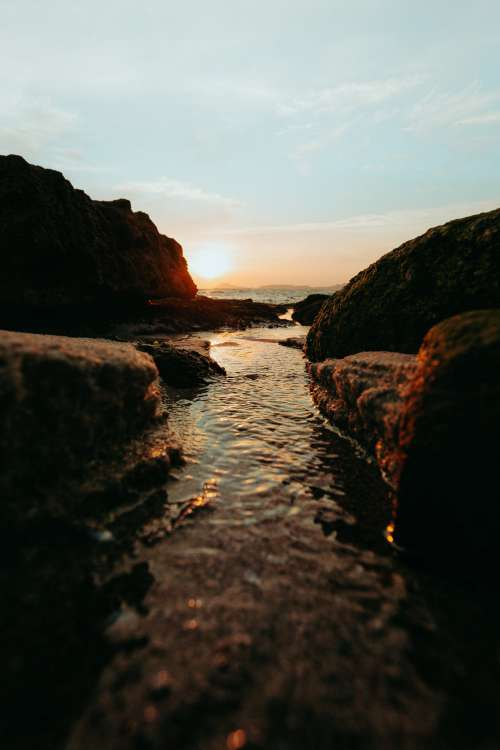 Stream Meets The Sea At Sunset Photo