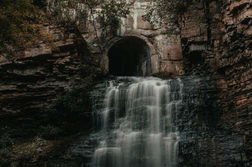 Tunnel Opens Out To Waterfall Photo