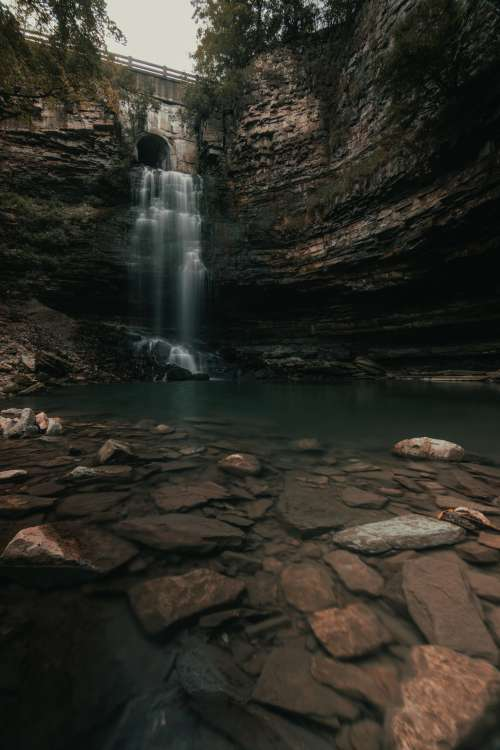 Bridge Overlooking Steep Rocks And Waterfall Photo