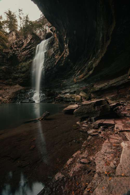 Concaved Rock Face By Waterfall Photo
